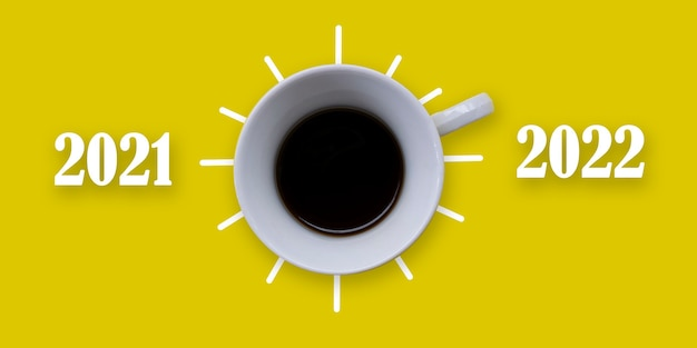 La tasse de café du nouvel an 2022 change de 2021 à 2022 sur fond jaune concept d'un nouveau départ