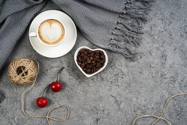 Tasse à café, écharpe, cerises et grains de café