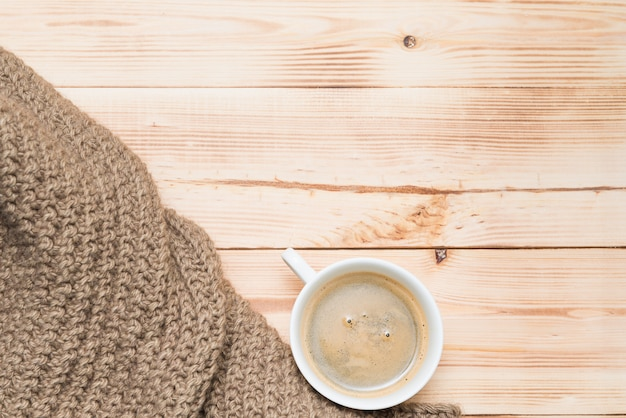 Une tasse de café avec une écharpe tricotée confortable sur une table en bois, vue de dessus. boisson, café, thème hygge