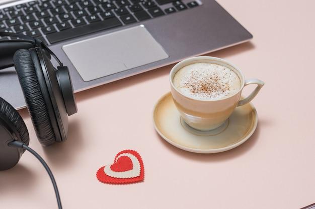 Une tasse de café, des écouteurs et un ordinateur portable sur une surface de corail