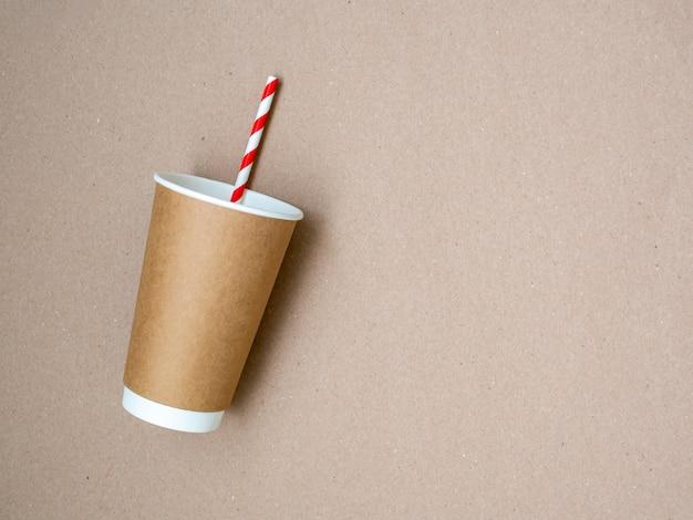 Tasse à café à emporter avec du papier paille blanche et rouge sur fond de papier craft. le concept d'un monde sans plastique et d'une planète propre. espace pour le texte. zero gaspillage. mise à plat, vue de dessus