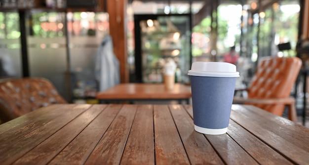 Tasse à café à emporter sur table en bois avec fond de café flou.