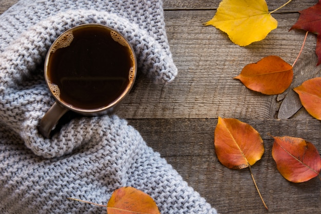 Tasse de café enveloppé dans une écharpe chaude sur une planche de bois.