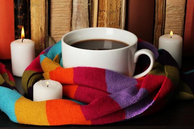 Tasse de café enveloppée dans une écharpe sur fond de livres