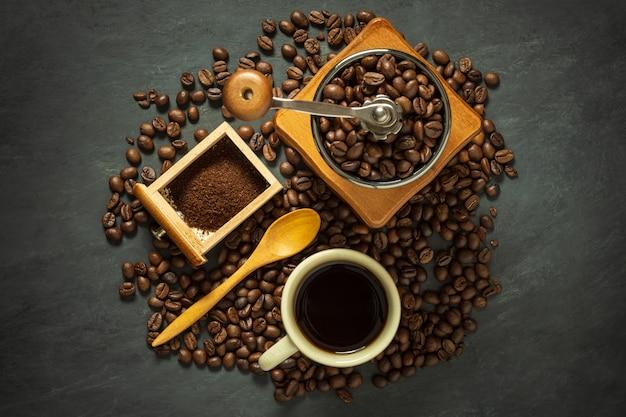 Tasse à café et équipement de café sur le sol en ciment noir.