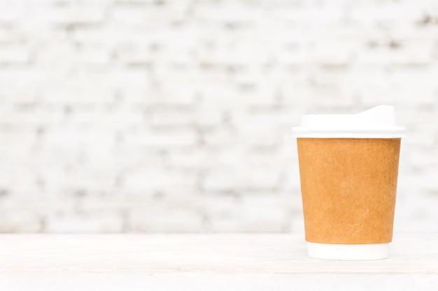 Tasse de café avec espace copie sur table contre fond de mur de briques blanches