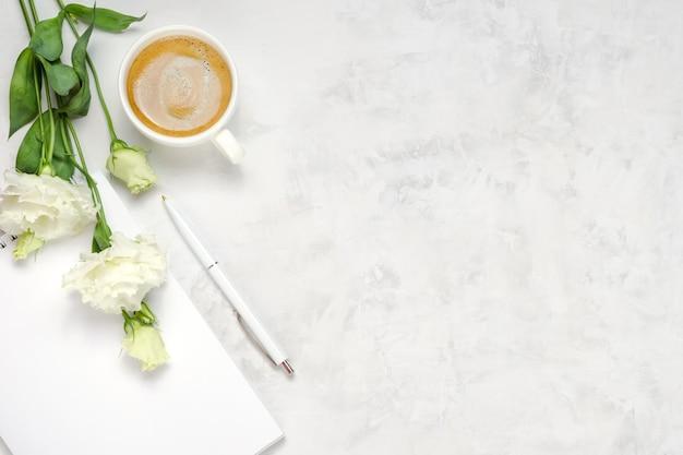 Tasse de café, eustoma, cahier et stylo sur fond de béton. vue de dessus à plat au-dessus. copier l'arrière-plan de l'espace