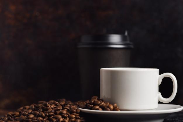 Tasse à café expresso blanc et grains torréfiés sur la vieille table brun rouillé