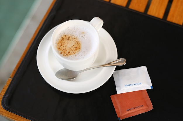 Tasse de café expresso avec des enveloppes de sucre sur la table en bois.