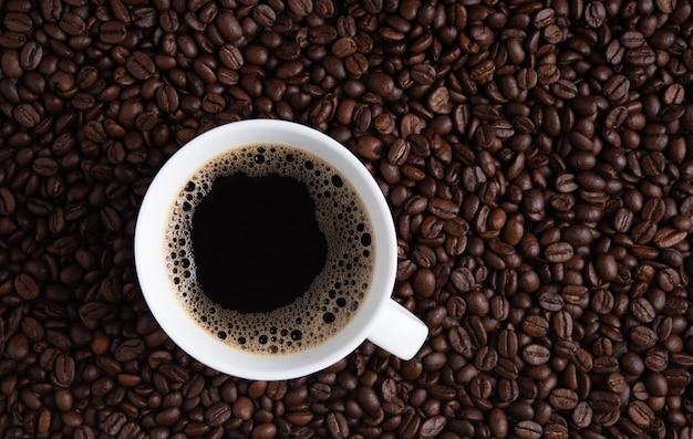 Tasse de café expresso sur les grains de café fond de texture de graine brune fond d'écran complet