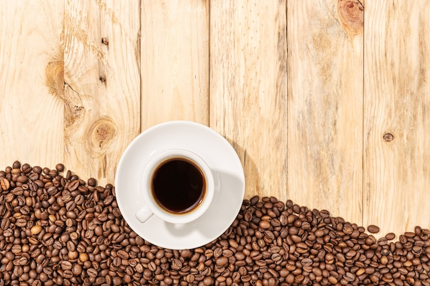 Tasse de café expresso et grains torréfiés sur fond de table en bois. copiez l'espace. vue de dessus