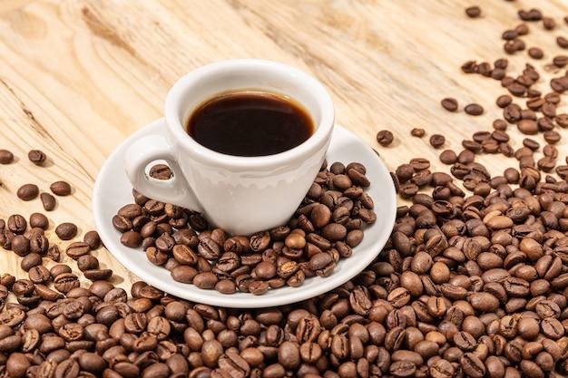 Tasse de café expresso et grains torréfiés sur table en bois. copiez l'espace.