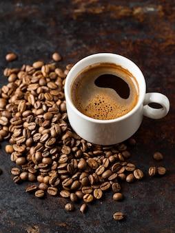 Tasse à café expresso et grains torréfiés sur vieux fond brun rouillé