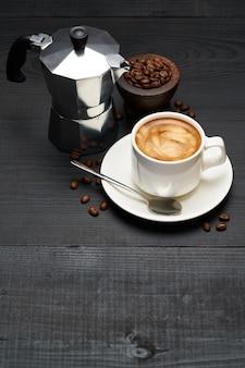 Tasse de café expresso et machine à café moka sur table en bois foncé