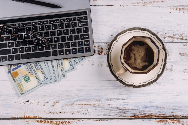 Tasse de café expresso noir sur le clavier de l'ordinateur et de l'argent en dollars américains dans la table en bois du bureau de l'espace de travail