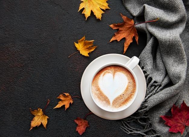 Tasse de café et feuilles sèches sur fond de béton noir.