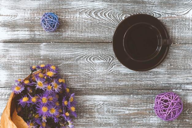 Tasse de café, fleur enveloppée dans du papier kraft sur la table grise vue du dessus. style pastel posé à plat.