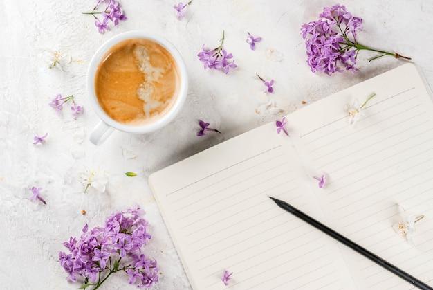 Tasse à café, fleurs et bloc-notes