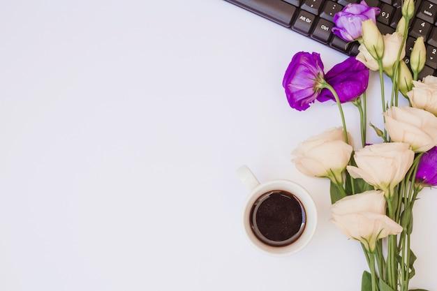 Tasse à café; fleurs eustoma blanches et violettes avec clavier sur fond blanc
