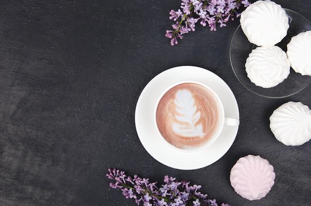 Tasse de café avec fleurs lilas et guimauves
