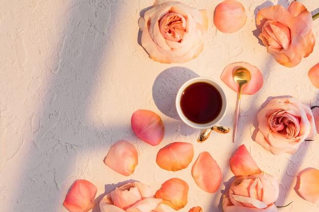 Tasse de café avec des fleurs roses roses et des pétales.