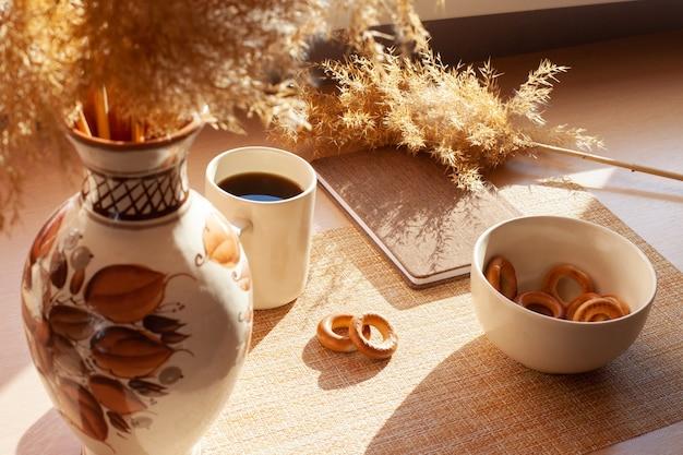 Une tasse de café, fleurs séchées, barankis, bloc-notes sur table en bois. marron et blanc.