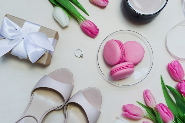 Tasse à café, fleurs de tulipes printanières et macarons roses sur table pastel vue de dessus verticale.