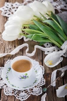 Tasse de café sur fond en bois ancien et un bouquet de tulipes blanches.