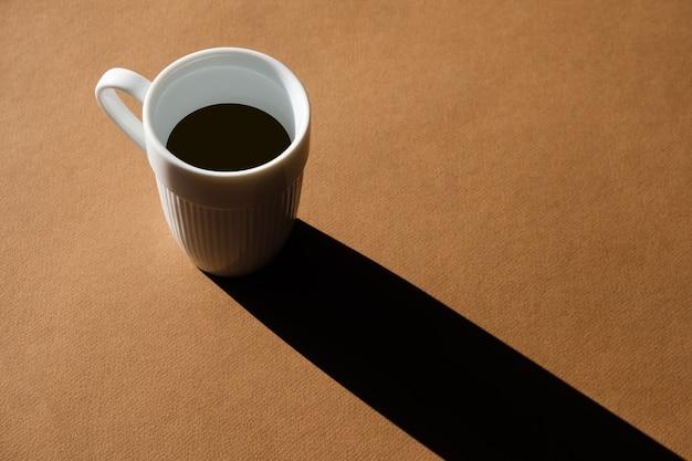 Une tasse de café sur fond marron projette une longue ombre