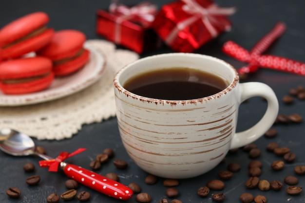 Une tasse de café sur un fond sombre avec des macarons de couleur corail