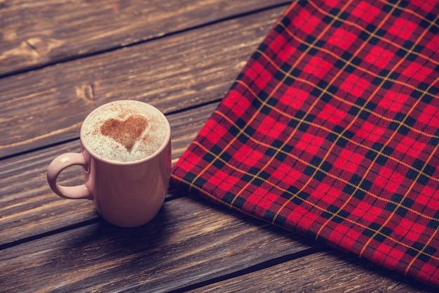 Tasse avec café et forme du coeur de cacao dessus et écharpe