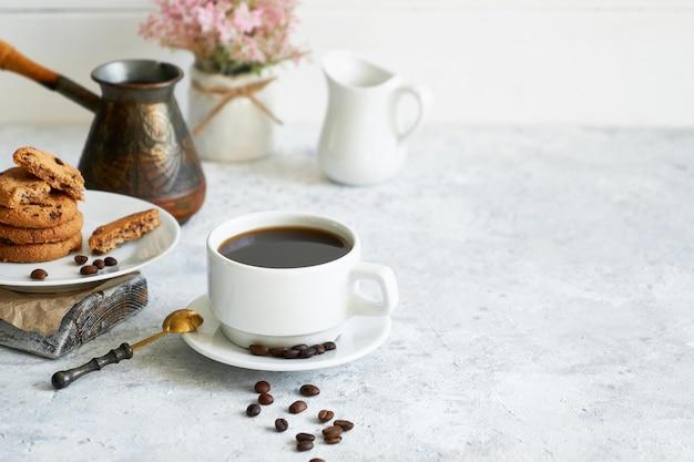 Tasse de café fort noir avec des grains de café et des biscuits