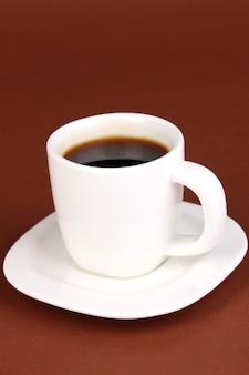 Une tasse de café fort sur une surface brune