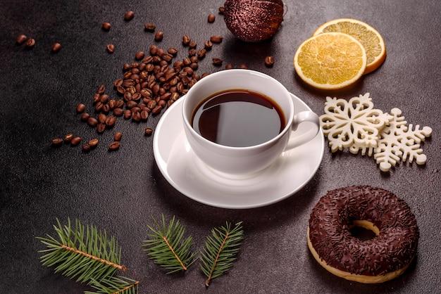 Une tasse de café fort sur la table de noël avec des brindilles d'épinette et des jouets. préparer les vacances