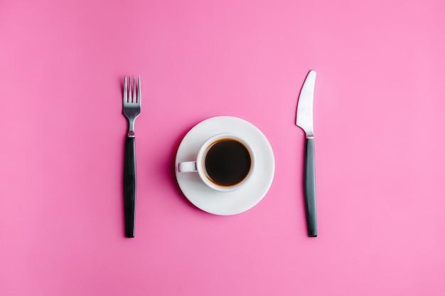 Tasse de café avec une fourchette et un couteau sur fond rose. aliments diététiques.