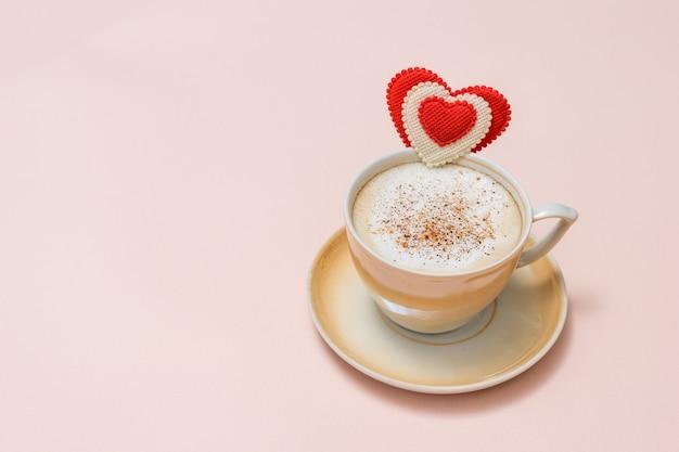 Une tasse de café frais avec de la cannelle et de la crème sur une surface rose