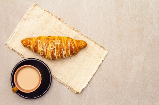 Une tasse de café frais avec un croissant. le concept sur un fond de pierre