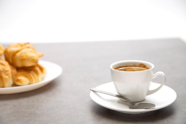 Tasse de café frais avec des croissants sur fond sombre