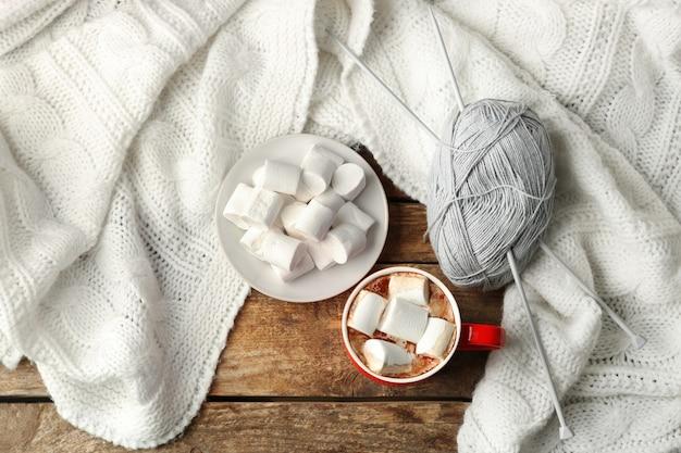 Tasse de café frais avec guimauve et plaid tricoté sur table en bois, vue du dessus