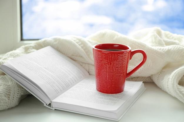 Tasse de café frais avec livre et plaid tricoté sur le rebord de la fenêtre