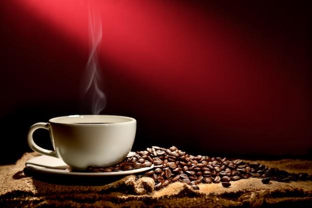 Tasse de café avec de la fumée et des grains de café sur fond brun rougeâtre