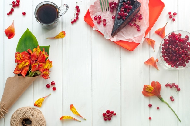 Tasse de café, gâteau et fleurs sur bois blanc