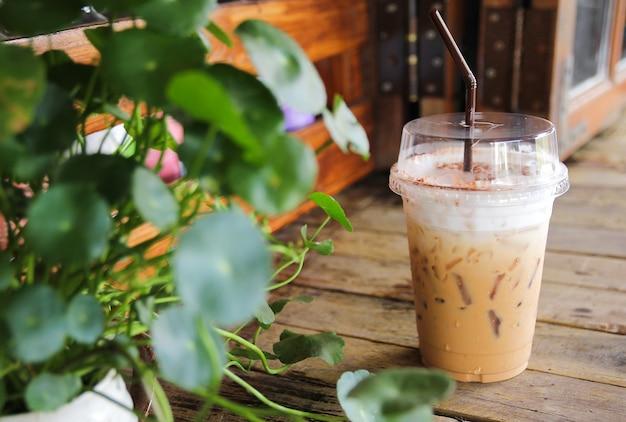 Tasse de café glacé sur le vieux bureau en bois avec feuille verte au premier plan