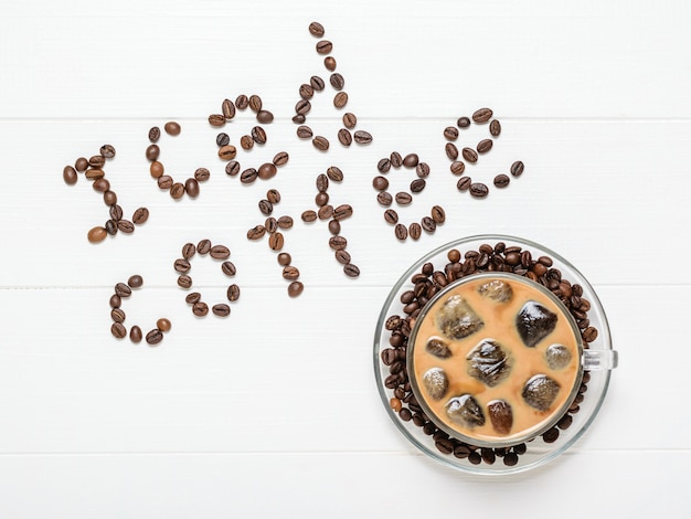 Une tasse de café avec des glaçons flottants et une inscription de café glacé sur une table blanche.