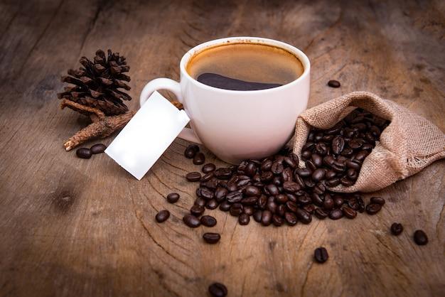 Tasse à café avec grain de café sur fond de bois, livre blanc pour texte