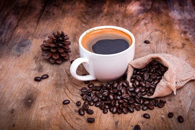 Tasse à café avec grain de café sur fond de bois