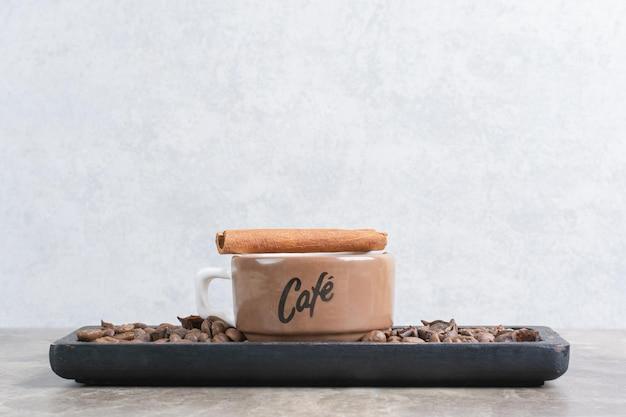 Tasse de café et de grains de café sur une assiette sombre.
