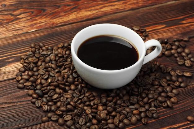 Tasse à café et grains de café sur bois