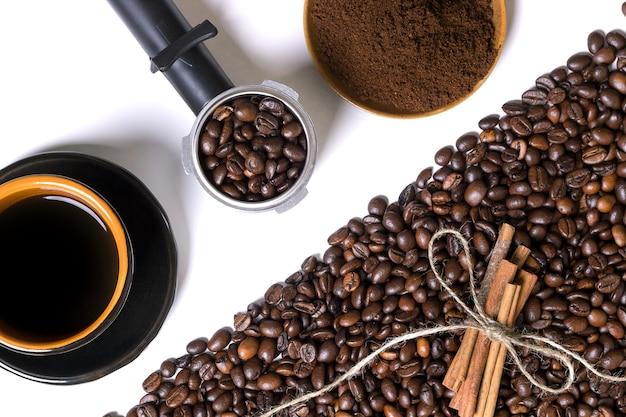 Tasse de café, grains de café, café moulu et cannelle sur fond blanc. vue de dessus. nature morte. espace de copie. mise à plat.