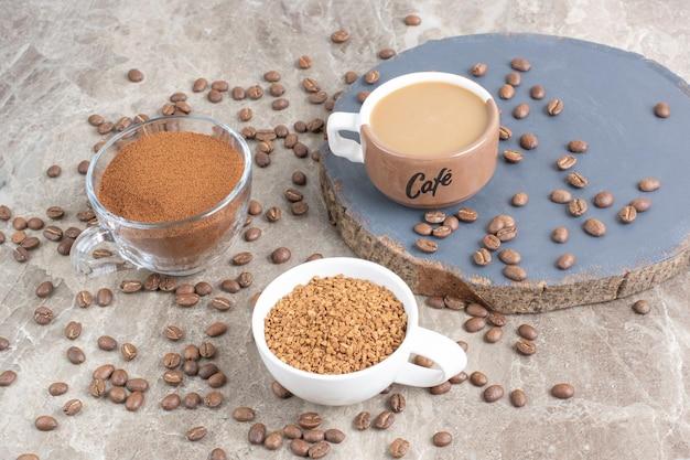 Tasse de café, grains de café et café moulu sur une surface en marbre. photo de haute qualité